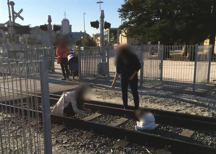 أم تضع طفلها على قضبان قطار لالتقاط صورة