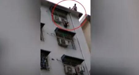 لحظة إنقاذ طفل معلق من رأسه في نافذة بالطابق السادس (فيديو)